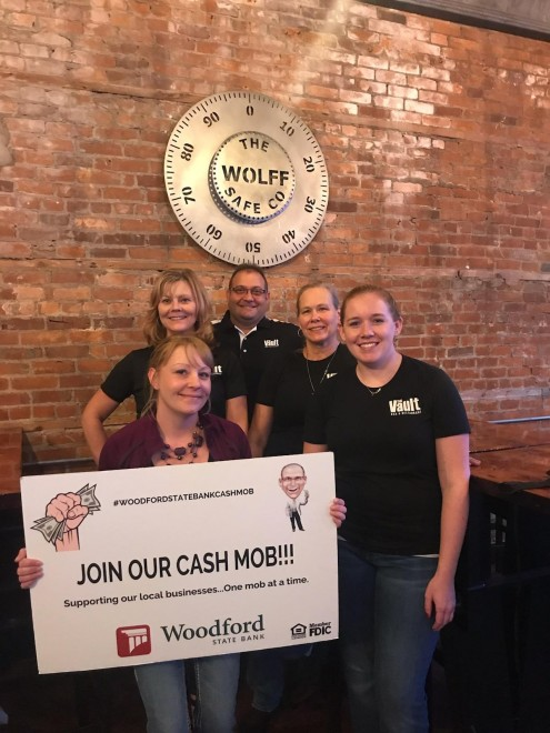 Picture of The Vault employees with a sign saying join our cash mob