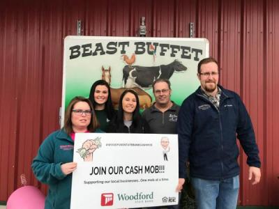 staff of beast buffet holding sign that says join our cash mob