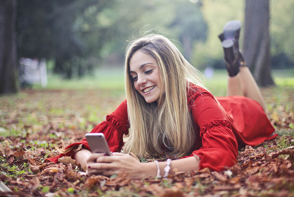 Image of a lady holding a phone laying on ground smiling